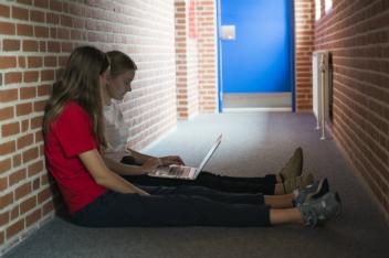 2 elever sidder med bærbar computer på gangen